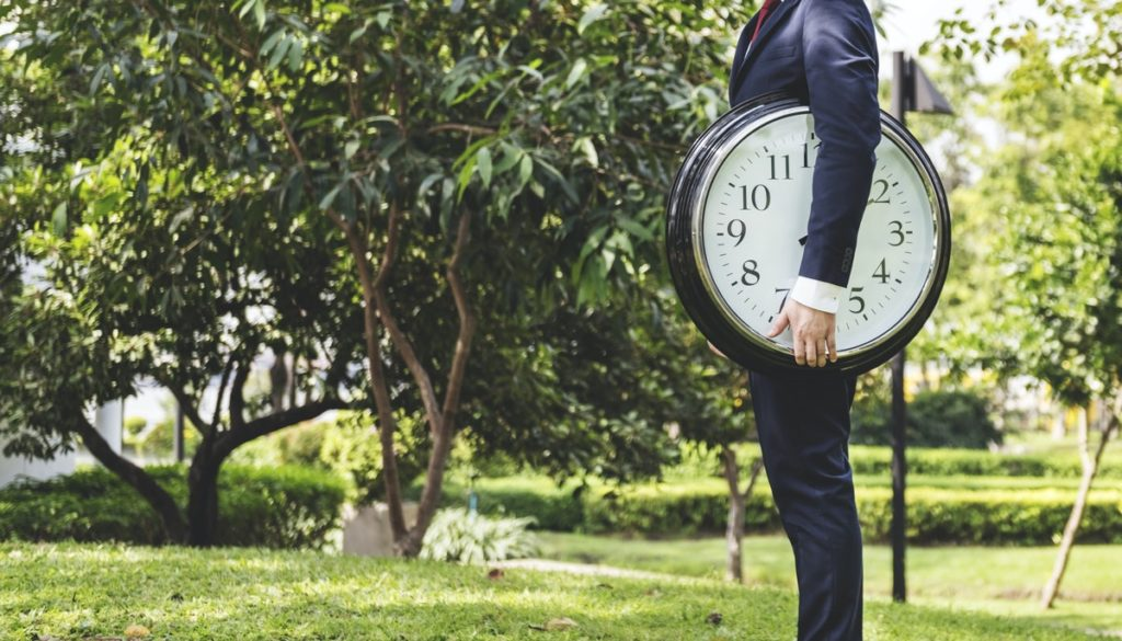 businessman standing outside holding giant clock