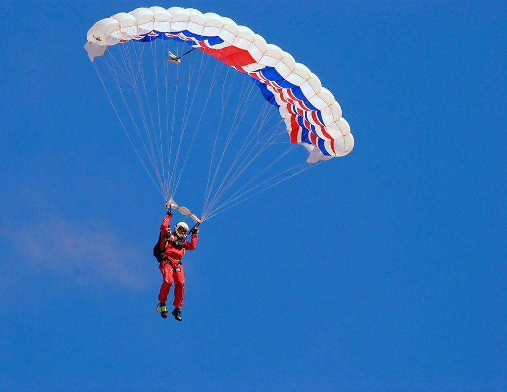 Parachuter lands, by Pexels